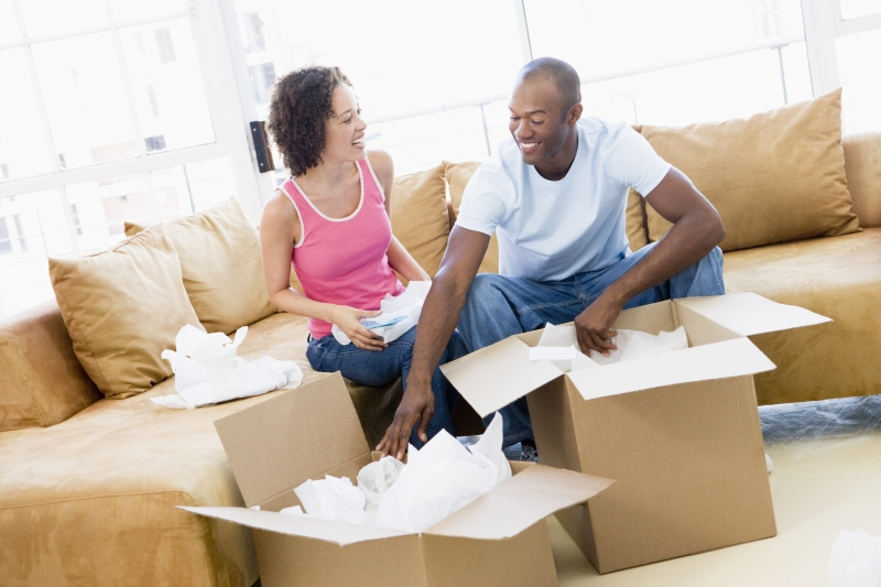 2166360-couple-unpacking-boxes-in-new-home-smiling